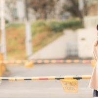踏切で待つ女性